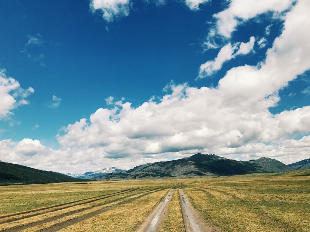 a dirt road in the grass leads to a mountain. There are blue skies but lots of clouds.
