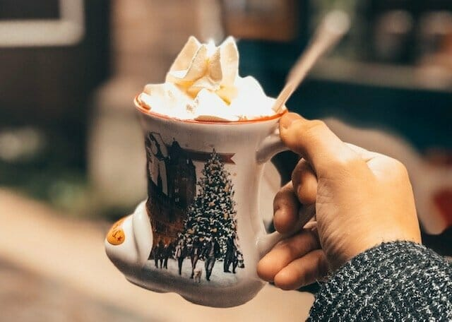 hot chocolate in a mug shaped like a boot, topped with whipped cream